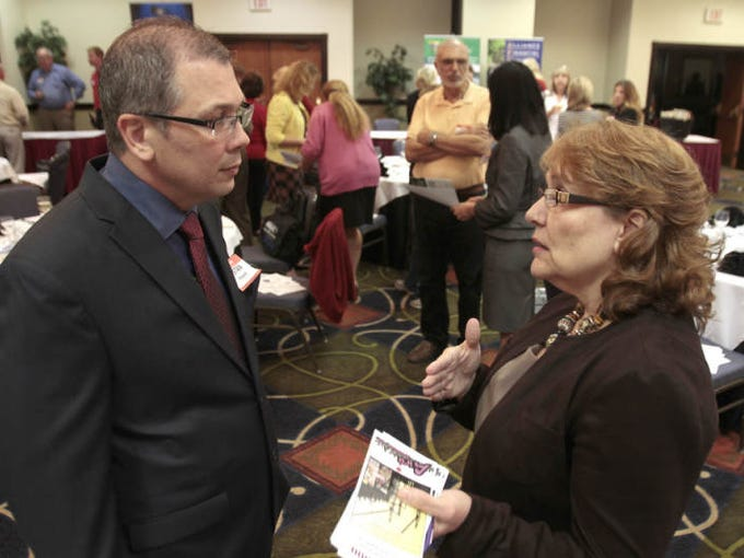 Stan Roland, Turner Construction Company Senior Project Engineer for the Hertz project, speaks with CoolAir Conditioning Marketing Coordinator Pat MaMantia at the National Association of Women in Construction event, held in Fort Myers Monday.