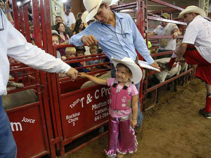 Ellie Olmstead, 4, of Hopkinton, Iowa gets a high-five while standing next to her father Brett Olmstead before participating in the Mutton Bustin' competition at the 2013 Iowa State Fair in Des Moines.