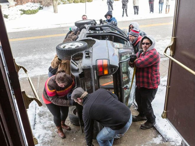 "The Phoenix Theatre stage crew lifts a car through the building's side entrance on East St. Clair Street. The car is a prop in Bruce Graham's new play, ""North of the Boulevard."""
