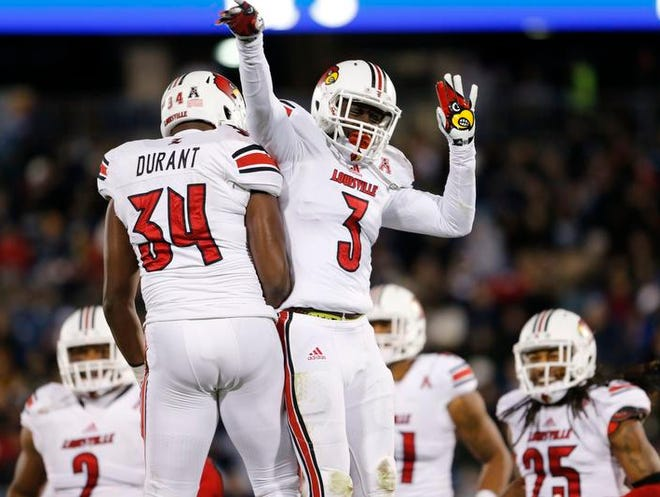 U of L cornerback Charles Gaines (3) reacts with teammate linebacker George Durant (34) after intercepting a pass intended for Connecticut Huskies wide receiver Shakim Phillips in the second quarter of last Friday's game at Rentschler Field.