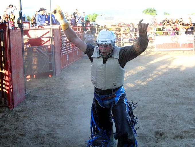Hayden Townsend, 18, reacts after riding an angry bull long enough to earn 72 points during rodeo action at the Marion County Fair on Thursday, July 3, 2014. The young man from Morral only started bullriding in March, much to his mother Robin Townsend's dismay.