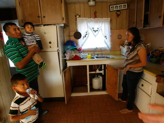 At La Cienega Mobile Home Park in Thermal in 2013, Huber Barrera, left, his kids Diego and David and wife Leticia Rioa show off their new filter to prevent arsenic consumption.