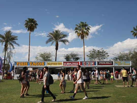 Fans walk by food stands during the Coachella Valley Music and Arts Festival on Friday, April 11, 2014 in Indio, Calif.