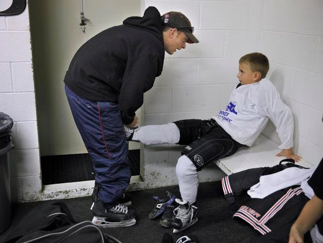 Amerks head coach Chadd Cassidy helps his son Sheldon, 7, tie his skates before practice with the Perinton Bulldogs, a youth hockey team for 7- and 8-year-olds at Thomas Creek Ice Arena. Cassidy is an assistant coach for his son's team.