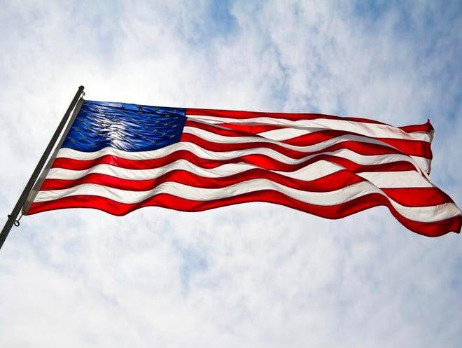 American flag with blue skies