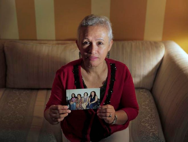 Merlita Snow of Gates holds a photo of herself with her two sisters and her mother together. A native of the Phillipines, Snow has not heard from her family members since the typhoon that struck the Phillipines last week. From left in the photo are Lorlie Cada, sister; Lilia Cada, mother; Bernadette Almejas, sister; and Merlita Snow.
