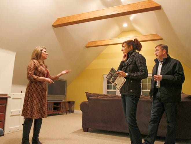 Beverly Howe, left, with Keller Williams Realty of Greater Rochester, shows a Dartmouth Street home to Linda and Will Weidman of Webster, during an open house last month. Open houses are brisk this winter due to rising interest rates, local brokers say.