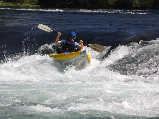 A kayaker runs Mill City Falls on the North Santiam River.