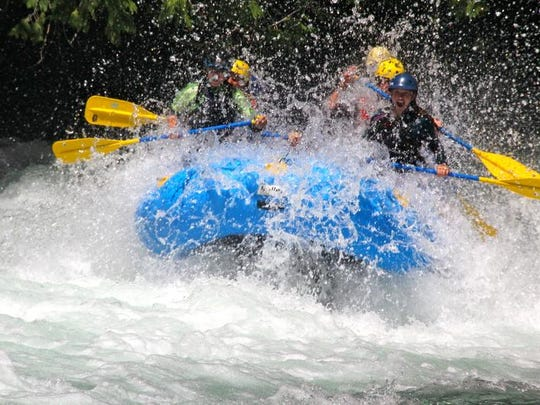 A group of rafters burst through a rapid on the White Salmon River.