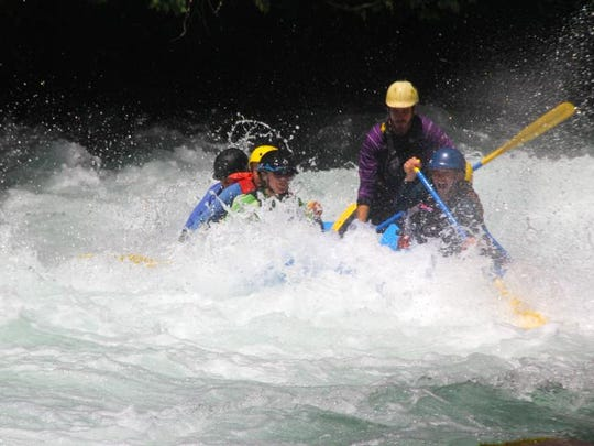 A group of rafters burst through the White Salmon River.