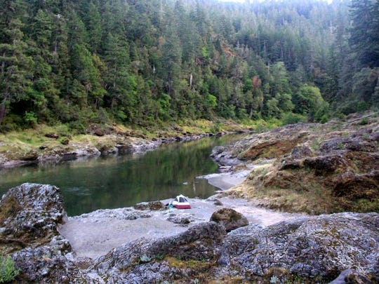 A camper sets down for the night along the Rogue River, just off the Rogue River Trail in the wild section between Grave Creek and Foster Bar.