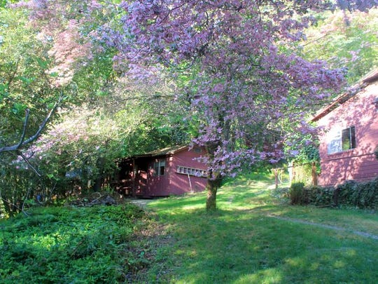 Marial Lodge has cabins among flowering trees where they spend the night along the wild section of the Rogue River.