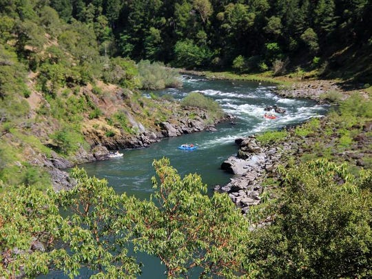 A group of rafters drop down a set of rapids on the wild section of the Rogue River.
