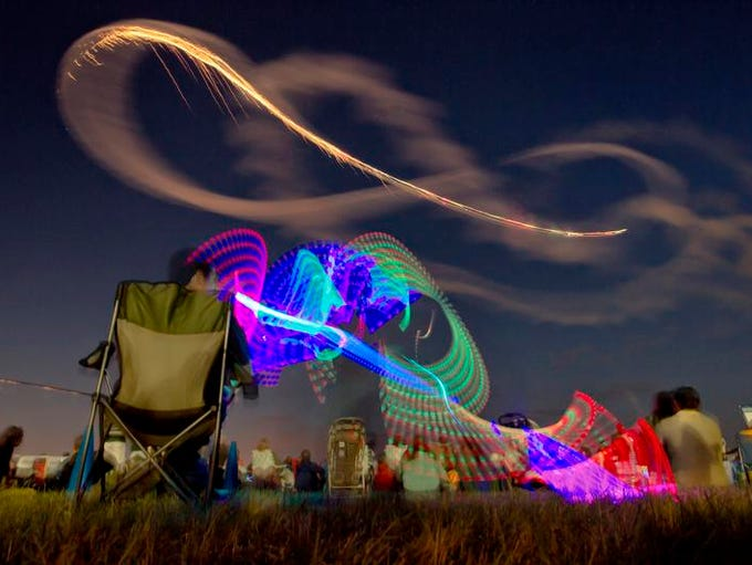A young boy twirls a light stick while an aerobatic pilot paints the sky with light at AirVenture's Saturday night airshow August 3, 2013.