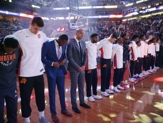 Phoenix Suns players huddle for the National Anthem