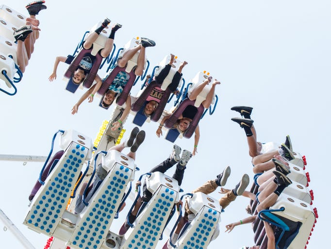 Fair goers hand upside down on Freak Out carnival ride