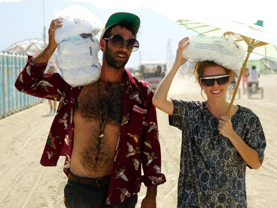 Patrick Scolnick, 34, and Bethany Rees, 31, both of Philadelphia, carry ice back to their camp after buying it at one of Burning Man's Arctica ice stores on Friday. Burning Man sells bags of ice for $4 each to help participants keep their food cold and reduce the risk of foodborne illnesses.