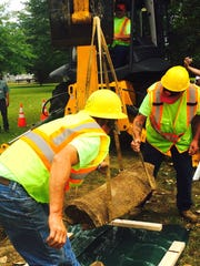 A bulldozer lifts a Revolutionary War cannon fragment Friday found at Red Bank Battlefield Park in National Park as Gloucester County public works employees (from left) John Geib and Chris Dolan guide it out of its burial site