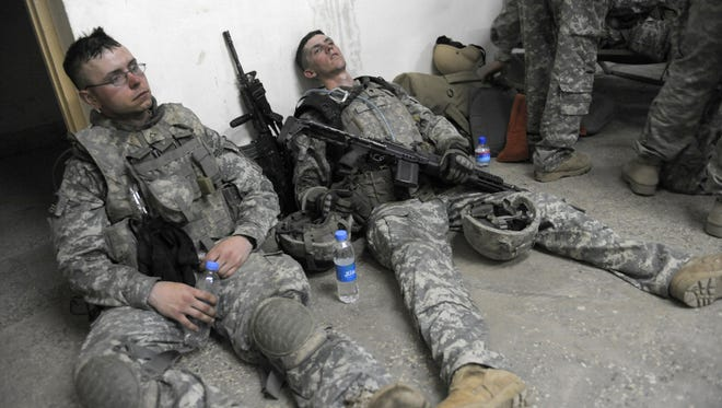U.S. soldiers from 1st Infantry Division lie exhausted on the floor at an operation post after completing a mission to search for weapons in the Alaugal valley in Nishagam, in Afghanistan's eastern Kunar province on April 10, 2009.