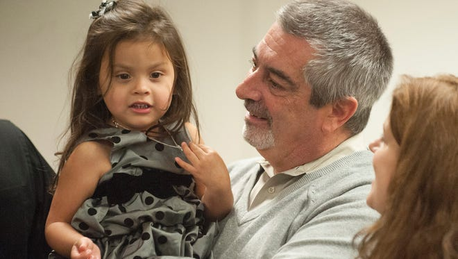 Oaklyn resident Dru Genther holds their daughter Sofia, 3, as his wife Jennifer (right) looks on during the Camden County Adoption Day celebration at the County Surrogate's Office in Camden. Friday, November 20, 2015.