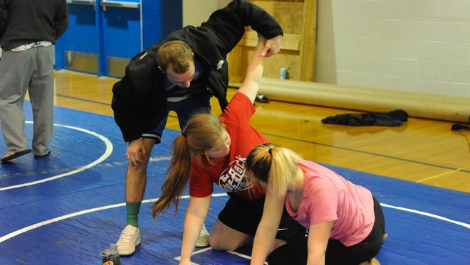 Fort Defiance assistant coach Isaac Diehl gives wrestling instruction to Kalie Grove, center, and Natalie Scott during practice Wednesday morning.