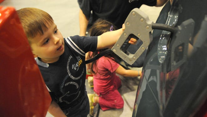 A young visitor pretends to pump gas at the Please Touch Garage at the Please Touch Museum in Philadelphia.