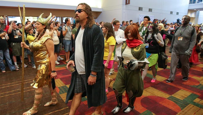 """Gen Con attendees, including Michael Smith as The Dude from """"The Big Lebowski,"""" take part in the costume parade during last year's convention."""