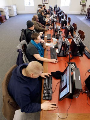 In this Feb. 19, 2015 photo, people work at public computers at the Nashville Public Library in Nashville, Tenn. Current laws regulating government access to private electronic communications are almost 30 years old.