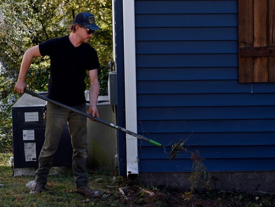 Derrick Royer cleans up old landscaping Friday, Oct.