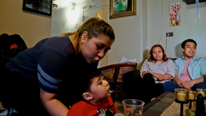 Rosa (second from right) an undocumented immigrant who wants her family's last name withheld, is surrounded by her son Edgar (far right) daughter Olga (far left) and grandson Logan at their home during an interview in New York. Rosa who used to get about $190 per month from the Supplemental Nutrition Assistance Program or SNAP, stopped taking benefits fearing deportation, and now gets by with the help of a local church and some family members.