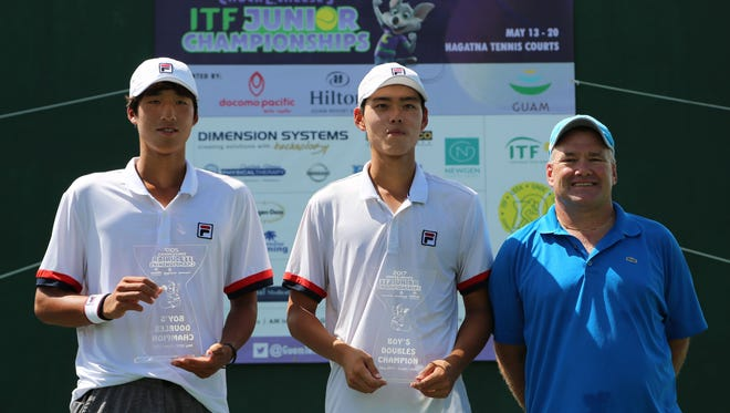 Korea Republic's Jeong Yeongseok (left) and Lee Jung Woo pose with the boys doubles event champions trophies of the 2017 Chuck E. Cheese's Guam ITF Junior Championships tennis tournament after the pair defeated Japan's Maruyama Syunya and Takahata Riku, 6-7(4), 6-3, 10-5 in the championship match Friday at the Rick Ninete Tennis Center in Hagåtña. Also in the photo is Torgun Smith, Guam National Tennis Federation President and tournament director.