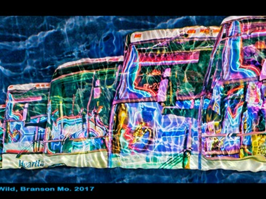"""""""Neon Buses Gone Wild,"""" by Josh Mitchell, shows a row of buses reflecting the neon on Shoji Tabuchi's theater in the rain."""