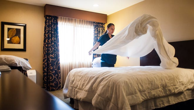 Housekeeper Amanda Russell makes a bed in the Heritage Inn.