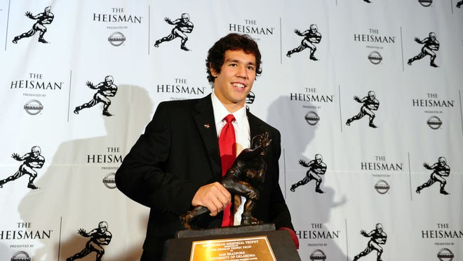Dec 13, 2008; New York, NY, USA; Oklahoma Sooners quarterback Sam Bradford poses with the Heisman Trophy as he addresses the media at the Sports Museum of America after being awarded the 2008 Heisman Trophy in New York City.  Mandatory Credit: James Lang-USA TODAY Sports