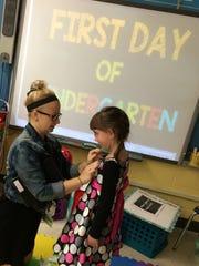 Weston Ele. - 8:26 a.m. Kindergarten teacher Katelyn Landerman puts an ID badge on student Alexis Mosure.