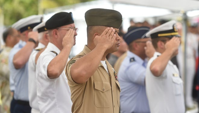 "In this May 29, 2017, file photo, military leaders stand at attention for the singing of the national anthem and ""Guam Hymn"" during a Memorial Day Commemoration at the Guam Veterans Cememtery in Piti."