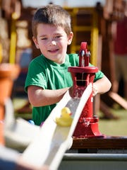 Tyler Wertish, 4, works the pump handle as fast as