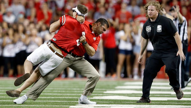 Ohio State strength and conditioning coach Anthony Schlegel tackles a person who ran onto the field.