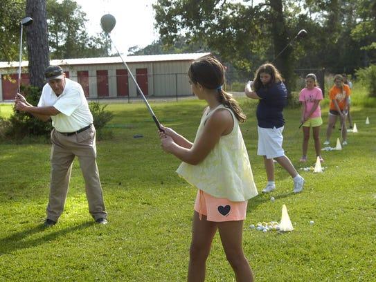Lou Dechert (left) teaches a girls golf class in 2014.