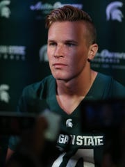 Michigan State quarterback Brian Lewerke talks with