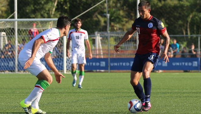 In this Nov. 17, 2015, file photo, Guam's Marcus Lopez controls the ball in the midfield against I.R. Iran.