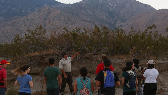 BLM archaeologist George Kline talks about the creosote bush during a nighttime wildlife hike in the desert near Snow Creek, July 11, 2017.