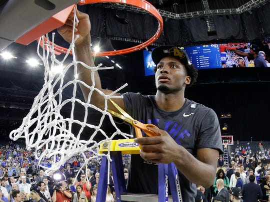 Duke's Justise Winslow cuts down part of the net Sunday after the Blue Devils beat Gonzaga in Houston to advance to the Final Four next weekend in Indianapolis.