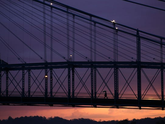 A person walks across the John A. Roebling Suspension