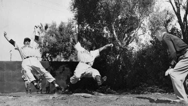 """Difference between being safe or out often depends on a slide,"" is how this Associated Press photo was captioned during the Chicago Cubs 1952 inaugural spring training season at Mesa Rendezvous Park.  The players are Fred Baczewski (left) and Bob Kelley."