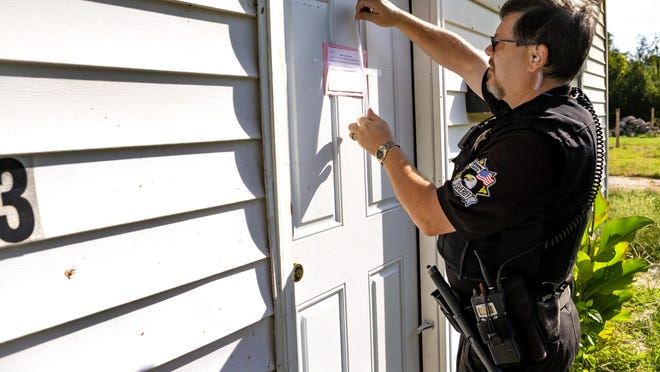 Oklahoma County Sheriff deputy, Brett Price, of the Field Services Bureau-Civil Division, serves an eviction notice and lock out at a rental house in Oklahoma City, Okla. on Tuesday, Sept. 10, 2019. [Chris Landsberger/The Oklahoman