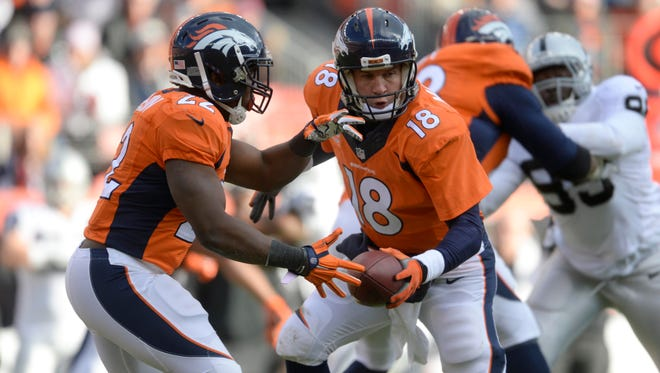Denver Broncos quarterback Peyton Manning (18) makes a play action move next to running back C.J. Anderson (22) in the first quarter against the Oakland Raiders at Sports Authority Field at Mile High. The Broncos defeated the Raiders 47-14.