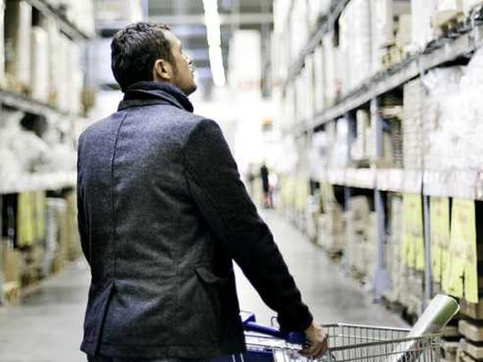 A man shops in a warehouse store with a cart.