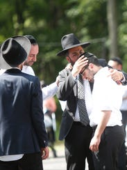 A Rabbi consoles a young man after leading the funeral