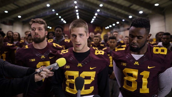 University of Minnesota wide receiver Drew Wolitarsky, flanked by quarterback Mitch Leidner, left, and tight end Duke Anyanwu stands in front of other team members as he reads a statement on behalf of the players in the Nagurski Football Complex Thursday.  The players delivered a defiant rebuke of the university's decision to suspend 10 of their teammates, saying they would not participate in any football activities until the school president and athletic director apologized and revoked the suspensions. If that meant they don't play in the upcoming Holiday Bowl against Washington State, they appeared poised to stand firm.